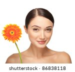 Portrait of beautiful smiling young woman with a flower. Taken in the studio. - stock photo