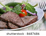 tender beef sirloin with black pepper seasoning, kosher salt and spinach - stock photo