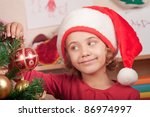 little girl in the hat of Santa Claus decorates a Christmas tree - stock photo