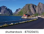 Main road on Moskenesoya island, Norway, with a typical red fisherman cottage - stock photo