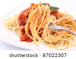 Spaghetti bolognese on a plate being eaten with a fork - stock photo