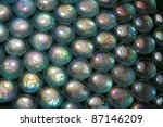 full frame abstract background picture with iridescent glass beads in dark back - stock photo