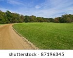 """""""Field and Trail"""" Blue skies, green grass and a dirt road, early Autumn in Central New Jersey. - stock photo"""