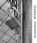 Lock and chain on fence gate illustrating security - stock photo