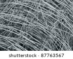abstract detail of a rolled mesh wire fence made of metal - stock photo