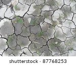 almost dry piece of clefty soil with litte grassy plants, seen from above - stock photo