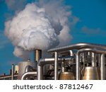 Detail of a factory with smoking chimney - stock photo