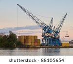 Two cranes are waiting for cargo in a dutch harbour - stock photo