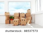 Kids having fun while moving in a new home playing with boxes - stock photo