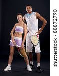 Two young tennis players standing with rackets in studio - stock photo