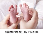 studio-shot of a mother showing newborn baby feet.  hands holding baby feet. - stock photo