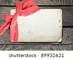 Grunge empty card and red bow on wood background - stock photo
