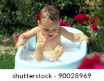 cute funny little boy bathing with bubbles outdoor in green garden - stock photo
