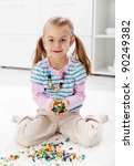 Look I made a necklace - little girl playing with beads - stock photo