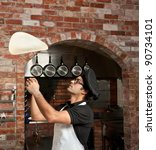 Pizza Chef makes the pizza dough spin in the air to make it thin and soft - stock photo