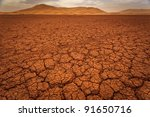 Cracked pattern of dry lake bed and sand dunes in Sahara Desert Morocco - stock photo