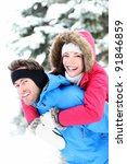 Happy winter couple piggybacking in snow smiling and joyful at camera. Beautiful young multi-ethnic couple, Asian mixed-race woman, Caucasian man doing piggyback. - stock photo