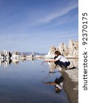 Reflection of young woman splashing water at Mono Lake, California! - stock photo