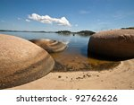 Rocks in still bay water - stock photo