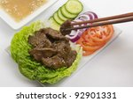 Cambodian (Loc Lac) / Vietnamese (Bo Luc Lac) stir-fried beef salad - Shaking Beef. Served with a lime and black pepper dip. - stock photo