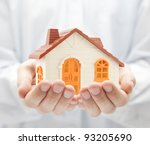 Small orange toy house in hands - stock photo