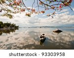 Cloudy sky reflected on still bay water - stock photo