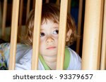 Sad little boy lying in a cage - stock photo