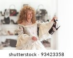 Humorous portrait of a medieval girl in modern footwear shop - stock photo