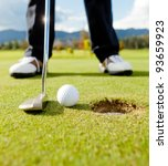 Golf player hitting the ball close-up on whole - stock photo
