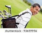 Man at the course carrying a golf bag - stock photo