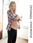 Young pregnant blonde getting dressed in front of window - stock photo
