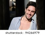 Portrait of young smiling man in urban background - stock photo