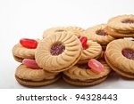 Sweet cookies with jam isolated on white with candy - stock photo