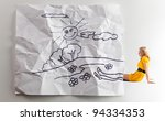 The young woman in a yellow dress and the rumpled children's drawing. - stock photo