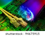electronic printed circuit board with network cable closeup on fiber optical background - stock photo