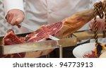 Chef slices serrano ham. Jamon Serrano. Typical Spanish delicatessen (prosciutto) - stock photo