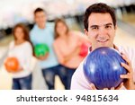 Man bowling with friends holding a ball and smiling - stock photo