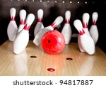 Bowling strike - ball hitting pins in the alley - stock photo