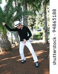 Dancing man in white hat in palm park. - stock photo