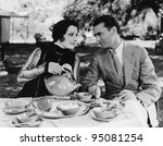 Couple having tea outdoors - stock photo