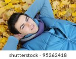 Young stylish man portrait laying in foliage in autumn park. Outdoor. - stock photo