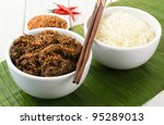 Beef Rendang & Sticky Rice - Malaysian/Indonesian spicy dry beef stew with coconut milk, topped with roasted dessicated coconut and served sticky rice. - stock photo