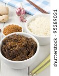 Beef Rendang & Sticky Rice - Malaysian/Indonesian  spicy dry beef stew with coconut, topped with roasted desiccated coconut and served with sticky rice. - stock photo