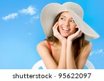 Beautiful woman with hat smiling on a background of blue sky - stock photo