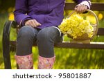 woman sitting on a bench with a trug of daffodils - stock photo