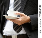 closeup of a businessman holding a cup of coffee - stock photo