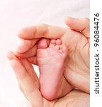 Newborn baby leg in careful hands - stock photo