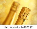 Champagne bottles over a defocused sparkling gold background - stock photo