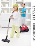 Kids cleaning the room - using vacuum cleaner and dust brush - stock photo