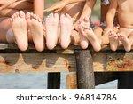 Children legs on the wooden pier - stock photo